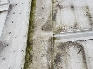 white dirty mouldy building roof before cleaning